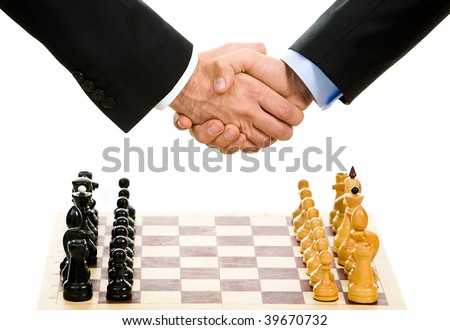 Image of chess-board with business handshake over it - stock photo