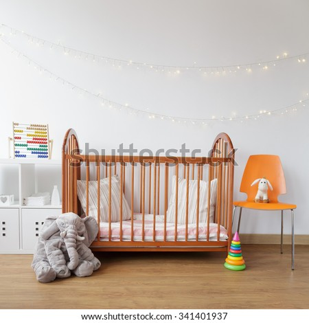 Image of child room with wooden crib and pink carpet - stock photo
