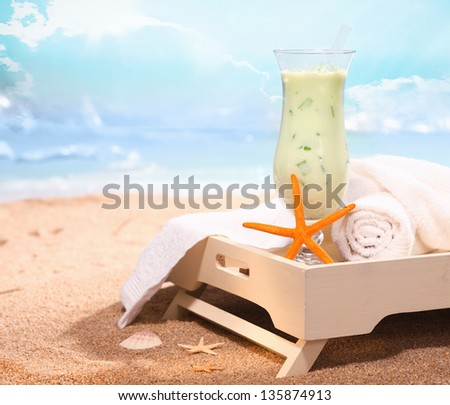 Image of chilled drink and some bath towels in white tray on the beach. Look at my portfolio for more cocktails. - stock photo