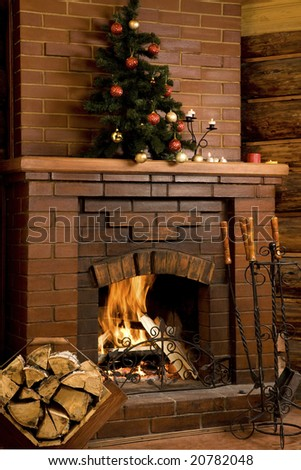 Image of chimney with fire inside and decorated tree on its top - stock photo