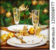 Image of Christmas dinner in restaurant, Christmastime table setting over decorated fir tree background, white plates served with knife and fork, two glass for champagne decorated with golden ribbon - stock photo