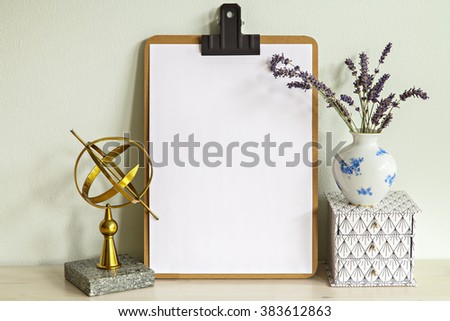 Image of clipboard mock up scene with vase, box and a brass sun dial.  - stock photo