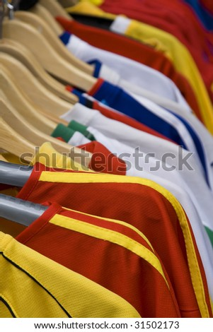 Image of colorful T-shirts on hangers in a street stand. - stock photo