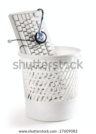 Image of computer keyboard with headphones in the trash bin - stock photo