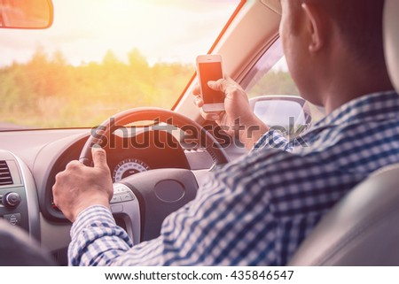 image of  Concept of dangerousman used cell phone while driving are dangerous for other people,blur image,transportation and vehicle concept - man using phone while driving the car,.lens flare  - stock photo