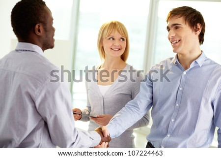 Image of confident business partners handshaking at meeting - stock photo