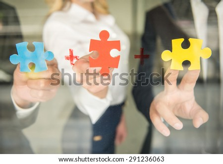 Image of confident business people wanting to put pieces of puzzle together. Close-up. - stock photo