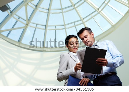 Image of confident businessman looking at document in partner?s hand while discussing it - stock photo