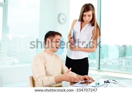 Image of confident businessman pointing at tablet with pretty colleague near by - stock photo