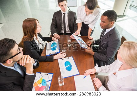 Image of confident colleagues communicating with their boss at meeting. - stock photo