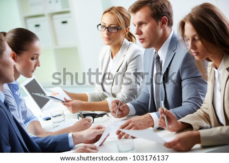 Image of confident man explaining something to his colleague at meeting - stock photo