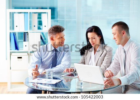 Image of confident partners discussing new project at meeting - stock photo