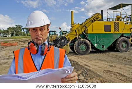 Image of construction manager or engineer at roadworks surveying plans - stock photo