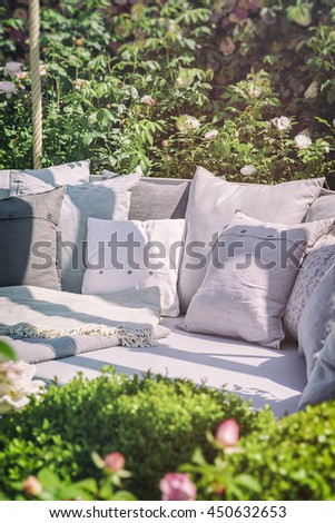 Image of cozy garden seating area with cushions. Vintage filtered.  - stock photo