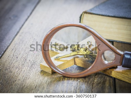 image of crucifix of Jesus Christ look through magnifying glass and  the holy bible on wooden background, concept - stock photo