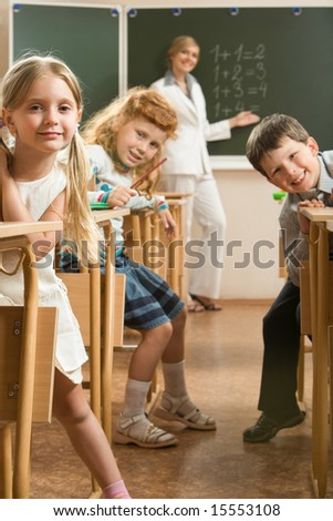 Image of curious schoolchildren sitting at the desk and looking at the camera in the classroom - stock photo