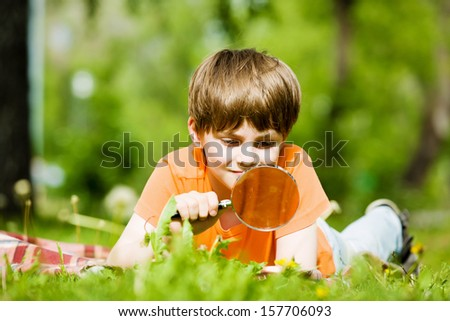 Image of cute boy playing in park with magnifier - stock photo