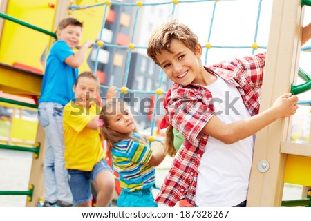 Image of cute kids having fun on playground outdoors, focus on smiling boy - stock photo