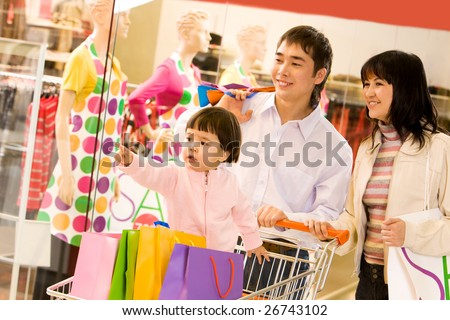 Image of cute toddler showing something to her parents in shop while they looking at it with smiles - stock photo