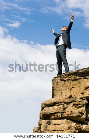 Image of delighted businessman standing on the mount peak with his arms raised - stock photo