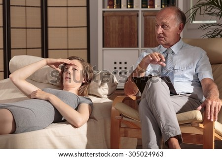 Image of depressed young woman during psychological treatment - stock photo