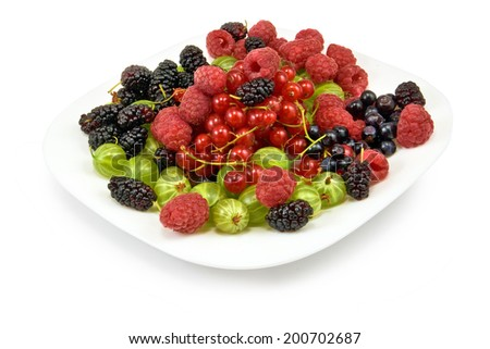 image of different berries in a plate on a white background closeup - stock photo
