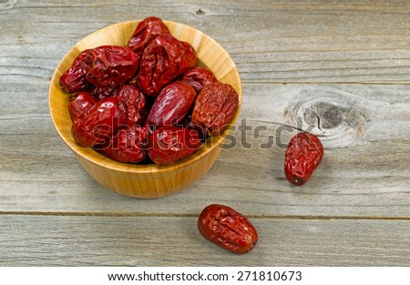 Image of dried dates in bowl on rustic wood. Layout in horizontal format.  - stock photo