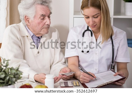 Image of elderly patient and doctor writing medical prescription - stock photo