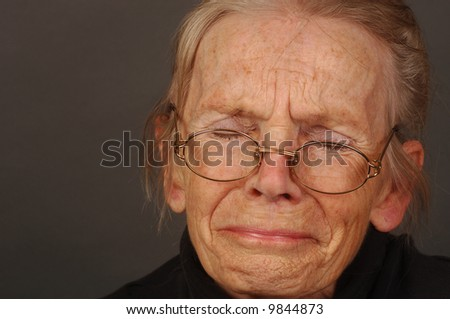 Image of Elderly woman with sorrow on Grey - stock photo