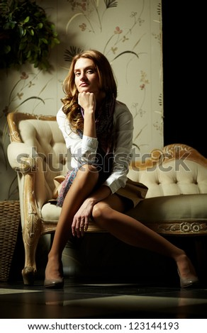 Image of elegant girl sitting in retro room and looking at camera - stock photo
