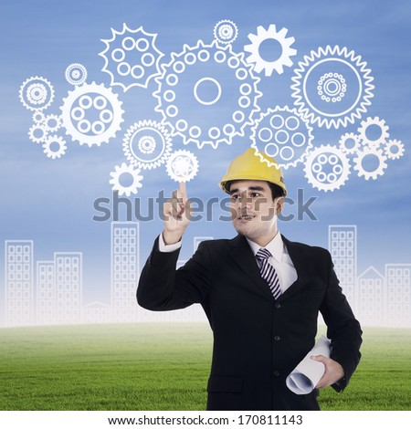 Image of engineer touching a gear elements. Mechanism concept - stock photo