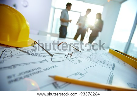 Image of engineering objects on workplace with three partners interacting on background - stock photo