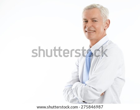Image of executive manager standing against white background with arms crossed and looking at camera. - stock photo