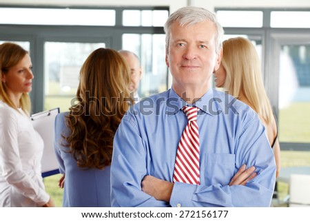 Image of executive manager standing with arms crossed an looking at camera while businesswomen consulting at background. Teamwork at office.  - stock photo