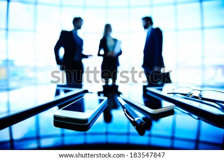 Image of eyeglasses, pen, cellular phones and touchpads at workplace with businesspeople having meeting on the background - stock photo