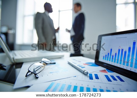 Image of eyeglasses, pen, touchpad and financial documents at workplace with businessmen communicating on background - stock photo