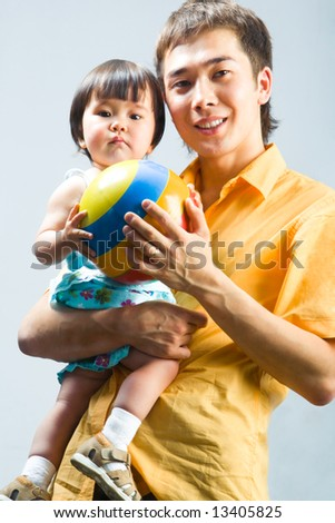 Image of father holding his little daughter and colorful ball - stock photo