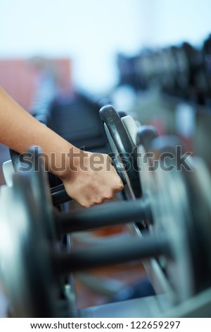 Image of female hand taking barbell from row of barbells in gym - stock photo