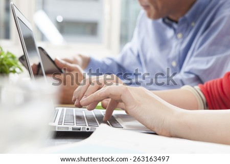 Image of female hands typing on keyboard in working environment - stock photo
