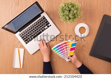 Image of female hands using color swatches for selection. Modern designer workplace. Concept of design working office. Modern workplace office. Top view - stock photo
