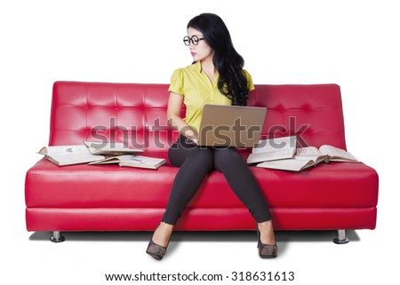 Image of female learner with casual clothes, studying with laptop and books while sitting on the sofa - stock photo