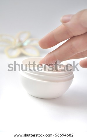 image of fingers taking hand cream with flower decoration on background - stock photo