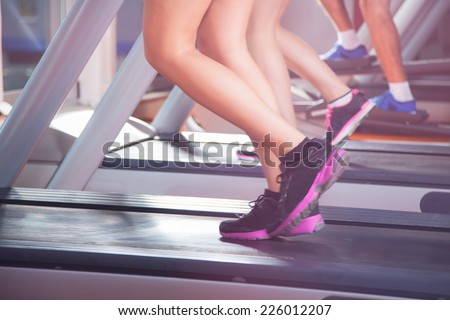 Image of fitness girl running on treadmill - stock photo
