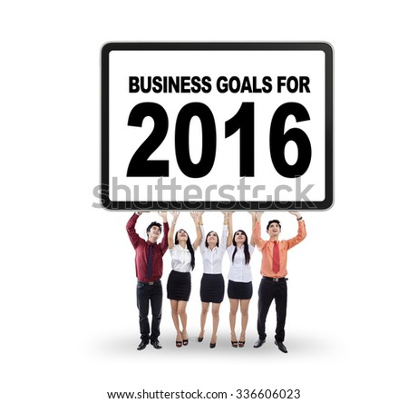 Image of five young businesspeople lift a big board with a text of business goals for 2016 - stock photo