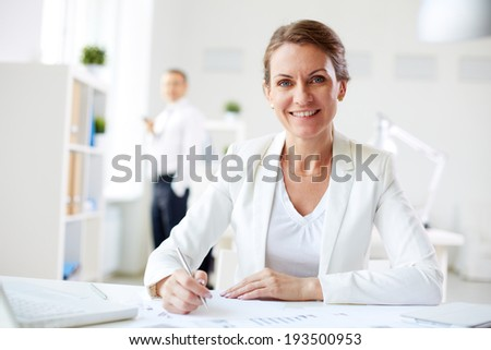 Image of formal businesswoman looking at camera at workplace - stock photo