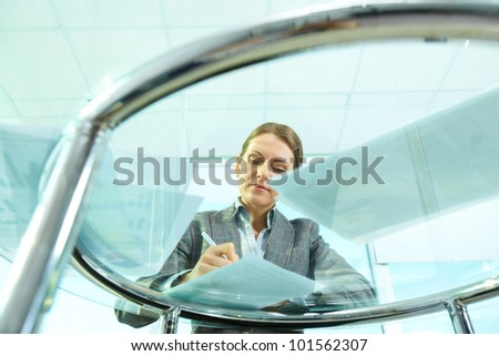 Image of formal businesswoman making notes on paper at workplace - stock photo