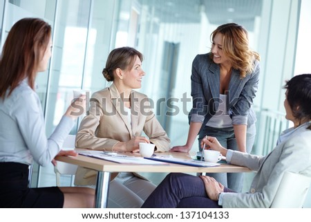 Image of four businesswomen interacting at meeting and having tea - stock photo