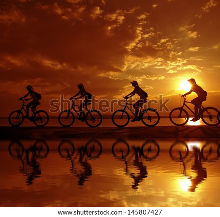 Image of four sporty company friends on bicycles outdoors against sunset. Silhouette A lot phases motion of a single cyclist along shoreline coast with reflection on water Copy space for inscription  - stock photo