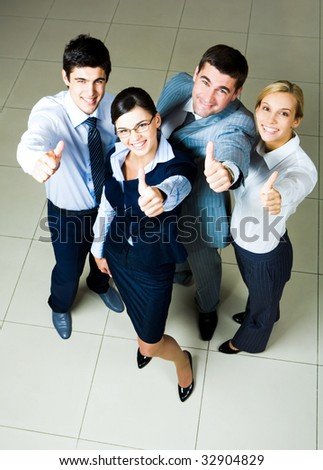 Image of four successful employees smiling at camera and showing thumbs up - stock photo