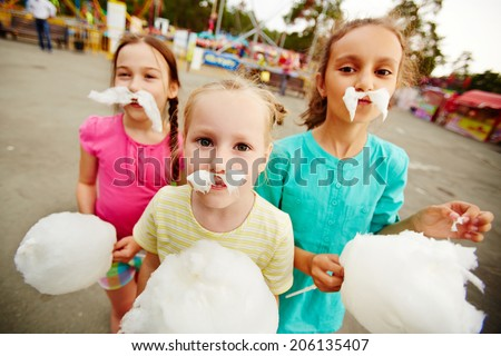 Image of funny girls with cotton candy posing on playground outdoors  - stock photo